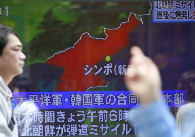 People walk by a TV news showing a map of North Korea with the location of the city of Sinpo while reporting North Korea's rocket launch, in Tokyo, Sunday, April 16, 2017