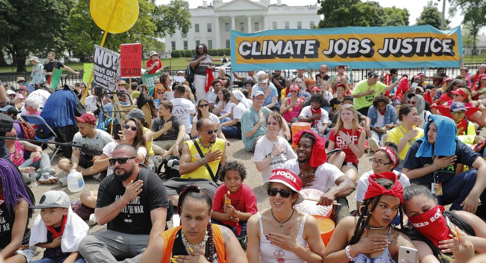 Demonstrators sit on the ground along Pennsylvania Ave. in front of the White House in Washington, Saturday, April 29, 2017, during a demonstration and march.