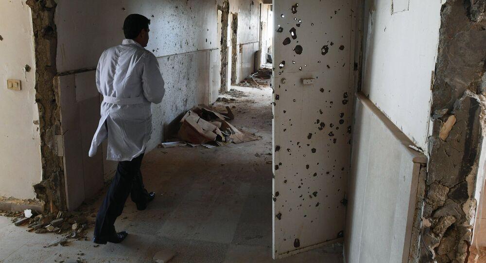 An employee in the corridor of Assad Hospital in Deir ez-Zor, Syria.