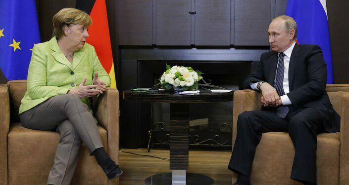 German Chancellor Angela Merkel talks to Russian President Vladimir Putin during their meeting at the Bocharov Ruchei state residence in Sochi, Russia, May 2, 2017