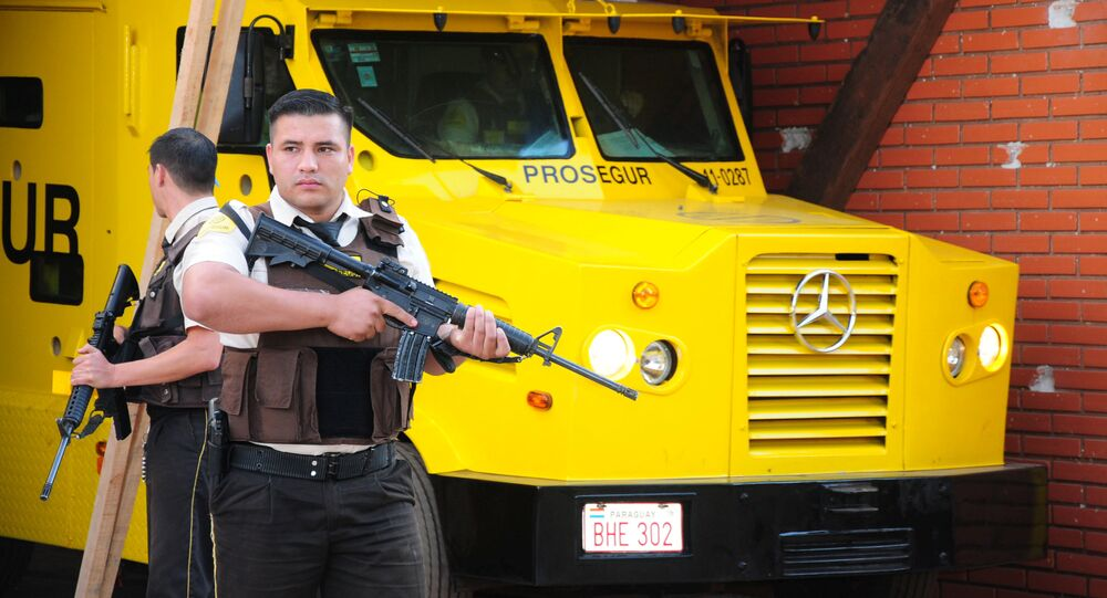 Security personnel stand guard next to an armored truck of private security company Prosegur after a gang of robbers carried out an assault on Monday with explosives and robbing millions of dollars, in Ciudad del Este, Paraguay April 25, 2017.