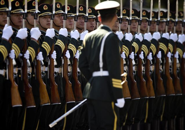 A Chinese People's Liberation Army soldier watches the position of members of a guard of honor as they prepare for a welcome ceremony for visiting Indian Prime Minister Manmohan Singh, outside the Great Hall of the People in Beijing Wednesday, Oct. 23, 2013.
