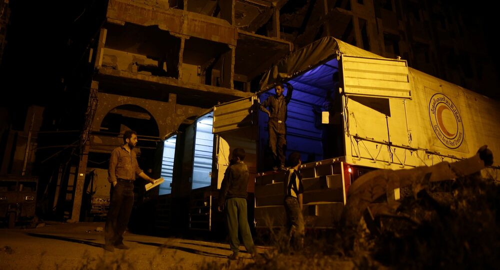 Relief workers unload parcels of humanitarian aid in the rebel-held besieged Syrian town of Douma, Damascus, Syria May 3, 2017. Picture taken May 3, 2017
