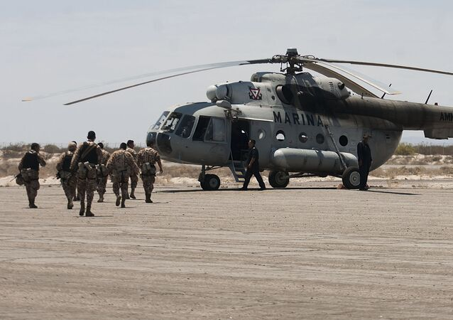 Mexican Navy marines prepare to board a helicopter as they continue their search and rescue efforts for survivors of a fishing boat accident in the town of San Felipe, Mexico, Tuesday July 5, 2011