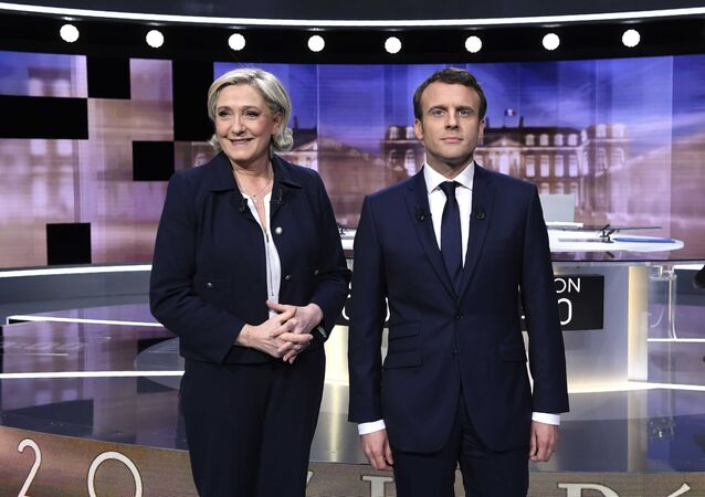 Candidates for the 2017 presidential election, Emmanuel Macron (R), head of the political movement En Marche !, or Onwards !, and Marine Le Pen, of the French National Front (FN) party, pose prior to the start of a live prime-time debate in the studios of French television station France 2, and French private station TF1 in La Plaine-Saint-Denis, near Paris, France, May 3, 2017