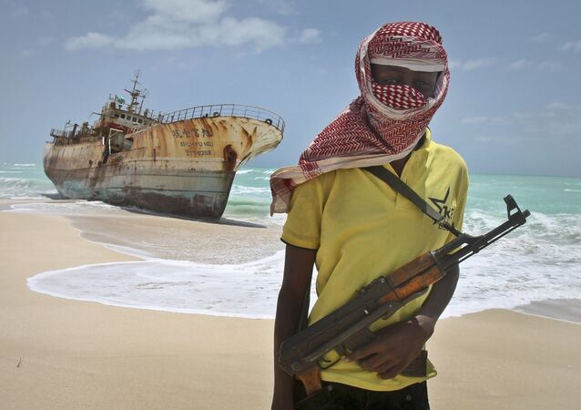 In this Sunday, Sept. 23, 2012 file photo, masked Somali pirate Hassan stands near a Taiwanese fishing vessel that washed up on shore after the pirates were paid a ransom and released the crew, in the once-bustling pirate den of Hobyo, Somalia.