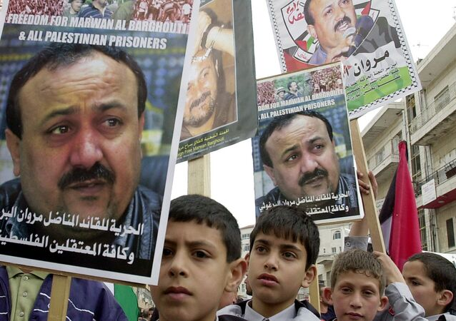 Palestinian youths hold pictures of Palestinian uprising leader Marwan Barghouti, detained in Israel, during a prisoners rally in the West Bank town of Ramallah Tuesday, April 15, 2003.