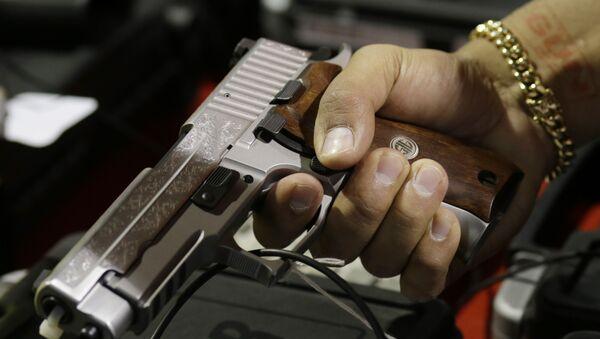 A customer looks at a SIG Sauer hand gun at a gun show held by Florida Gun Shows, Saturday, Jan. 9, 2016, in Miami.  - Sputnik International