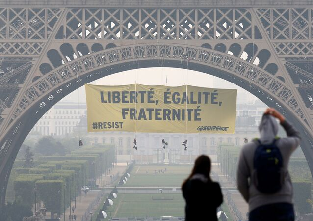 Tourists walk at Trocadero square as activists from the environmentalist group Greenpeace unfurl a giant banner on the Eiffel Tower which reads Liberty, Equality, Fraternity in a call on French citizens to vote against the National Front (FN) presidential candidate Marine Le Pen, in Paris, France May 5, 2017