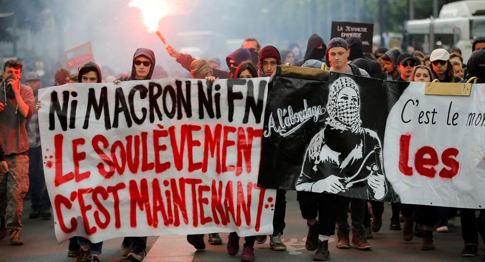 Youths walk behind a banner which reads,Neither Macron, Nor Le Pen - The Uprising is Now at a demonstration to protest the results of the first round of the presidential election in Nantes, France, April 27, 2017