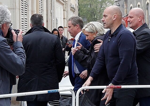Marine Le Pen (C), French National Front (FN) candidate for 2017 presidential election and Debout La France group former candidate Nicolas Dupont-Aignan, leave by a backdoor from the Cathedral in Reims, surrounded by bodyguards, France, May 5, 2017