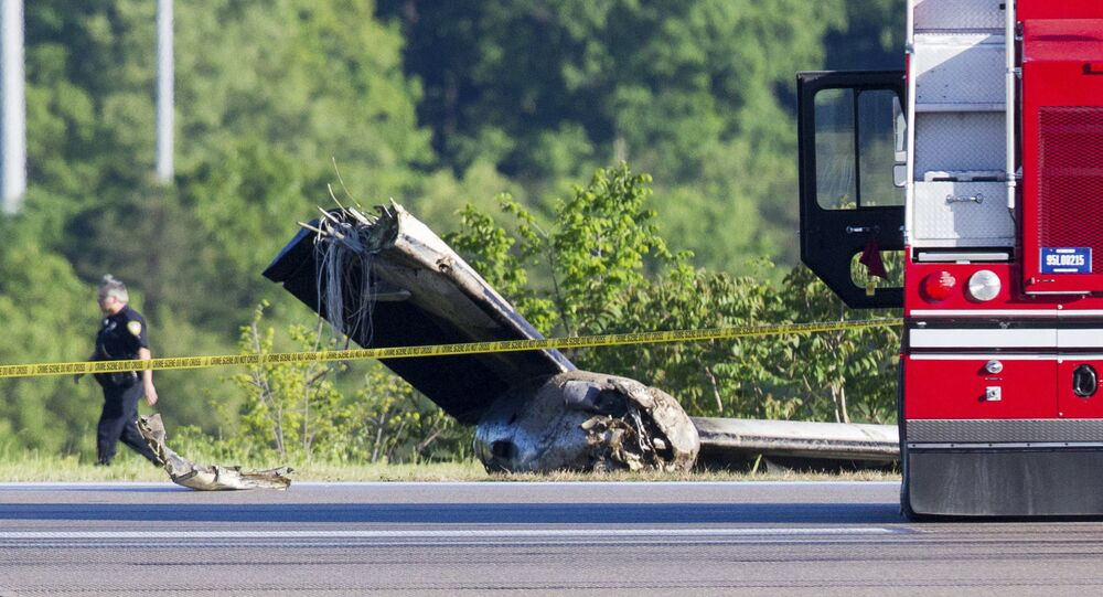 An officer walks near part of a cargo plane following a fatal crash at Yeager Airport in Charleston, W. Va., Friday, May 5, 2017