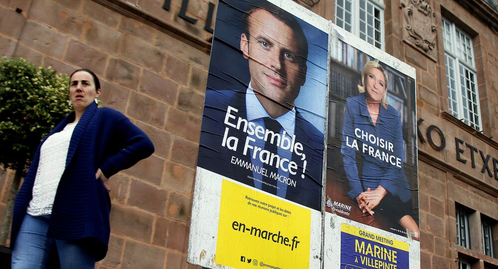 A woman walks near election campaign posters for French centrist presidential candidate Emmanuel Macron, left, and far-right candidate Marine Le Pen, in Saint Jean Pied de Port, southwestern France, Friday May 5, 2017