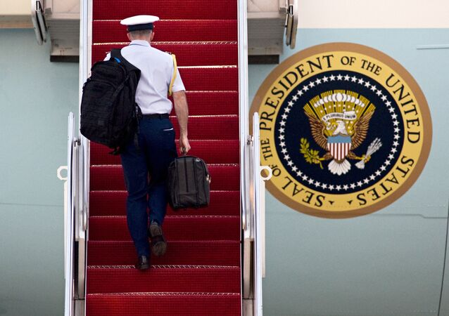 A Military aide carries 'the football', the leather briefcase stocked with the classified nuclear war plan, in his right hand as he walks up the stairs of Air Force One at Andrews Air Force Base, in Md.