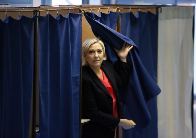 French far-right presidential candidate, Marine Le Pen exits a voting booth before casting her ballot in Henin Beaumont, France