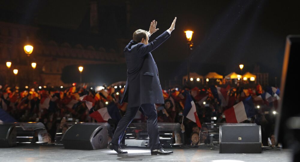 French president-elect Emmanuel Macron waves at supporters as he arrives on stage before delivering a speech in front of the Pyramid at the Louvre Museum in Paris on May 7, 2017, after the second round of the French presidential election.