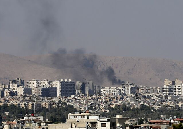 This Friday, August 23, 2013 file photo, black columns of smoke from heavy shelling in Barzeh, a suburb of Damascus, Syria.