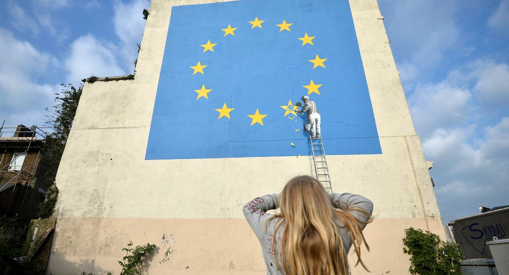 A young girl looks at artwork attributed to street artist Banksy, depicting a workman chipping away at one of the 12 stars on the European Union, seen on a wall in the ferry port of Dover, Britain, May 7, 2017.