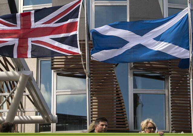 A Scottish Saltire (C) flies between a Union flag (L) and a European Union (EU) flag in front of the Scottish Parliament building in Edinburgh, Scotland on June 27, 2016.