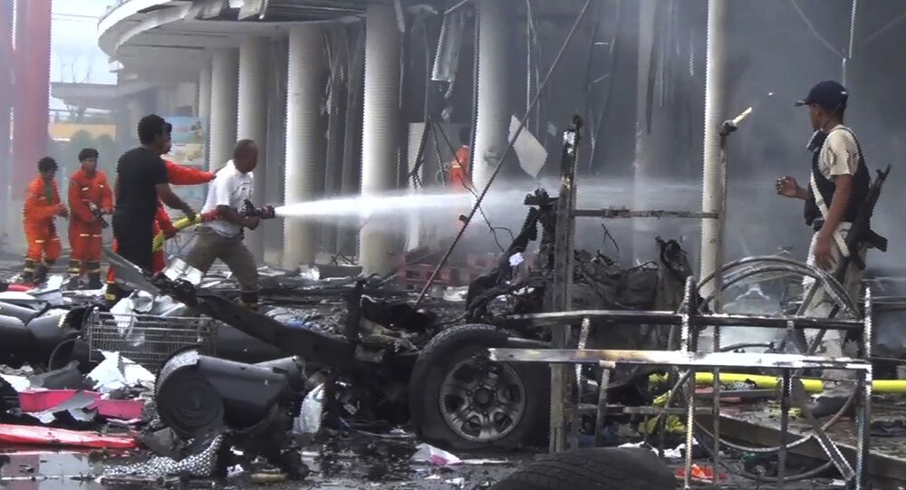 Firefighters try to extinguish the fire after a bomb hidden in a car exploded outside a large shopping center in Pattani province, southern Thailand