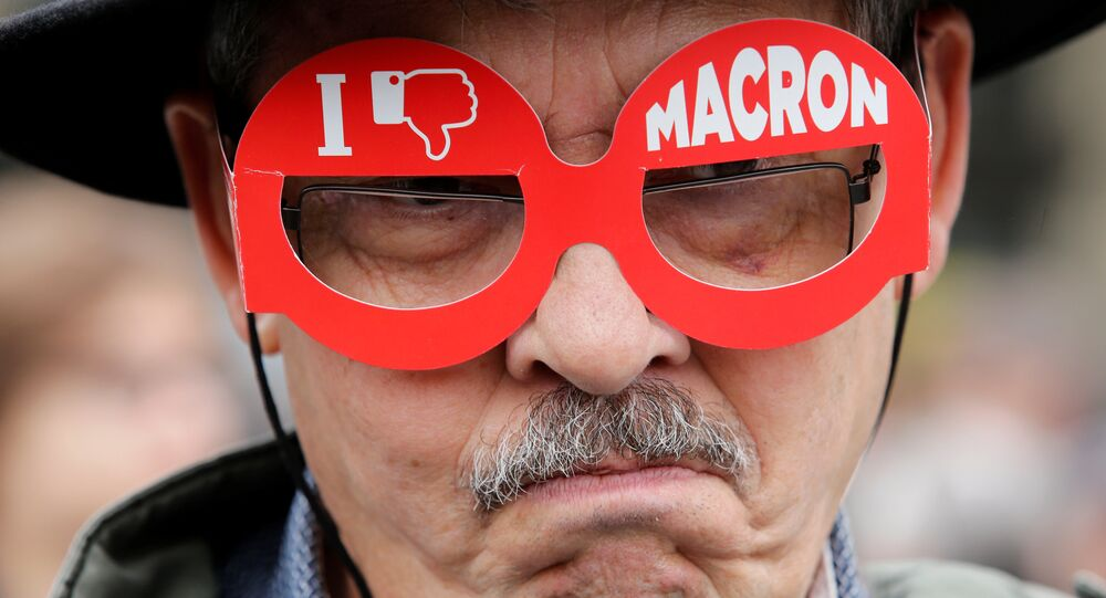 A demonstrator wears cardboard glasses with the message, I don't like Macron, in refererence to French president-elect Emmanuel Macron, as people gather to protest the day after the country went to the polls, in Paris, France, May 8, 2017.