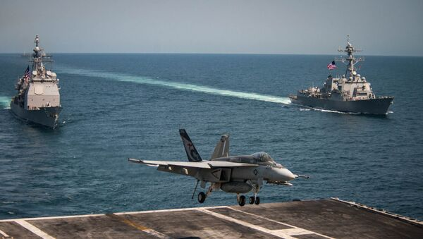 An F/A-18E Super Hornet lands on the flight deck of the U.S. Navy aircraft carrier USS Carl Vinson as the Ticonderoga-class guided-missile cruiser USS Lake Champlain (L) and the Arleigh Burke-class guided-missile destroyer USS Wayne E. Meyer transit the western Pacific Ocean May 3, 2017. - Sputnik International