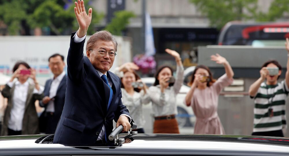 South Korean President Moon Jae-in waves as he heads for the Presidential Blue House in Seoul, South Korea, May 10, 2017.