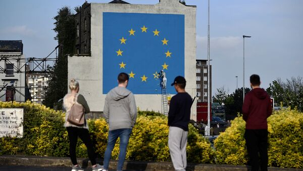 An artwork attributed to street artist Banksy, depicting a workman chipping away at one of the 12 stars on the flag of the European Union, is seen on a wall in the ferry port of Dover, Britain May 7, 2017. - Sputnik International