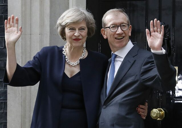 British Prime Minister Theresa May and her husband Philip wave from the steps of her official residence,10 Downing Street in London, Wednesday July 13, 2016.