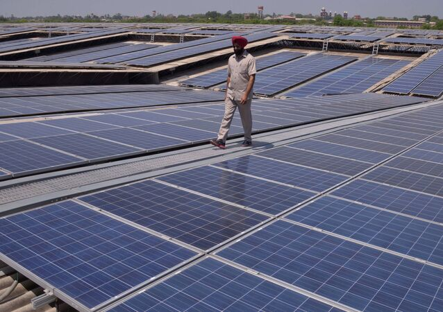 An Indian security personnel poses for media as he walks over rooftops covered in solar panels at the Solar Photovoltaic Power Plant, some 45kms from Amritsar. (File)