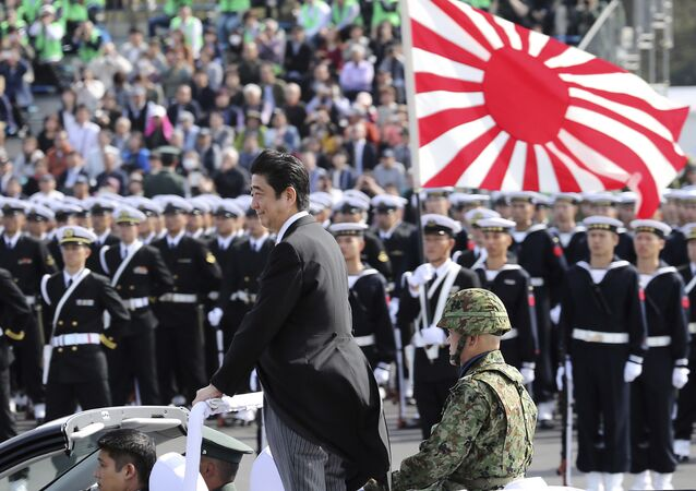 Japanese Prime Minister Shinzo Abe, center standing, reviews members of Japan Self-Defense Forces (SDF) during the Self-Defense Forces Day at Asaka Base, north of Tokyo, Sunday, Oct. 23, 2016.