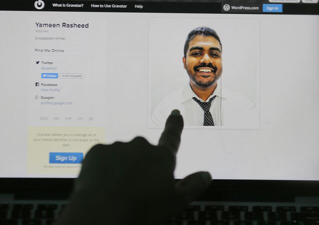 A Sri Lankan woman points to a portrait of Maldivian blogger Yameen Rasheed on his blog The Daily Panic in Colombo, Sri Lanka, Sunday, April 23, 2017.