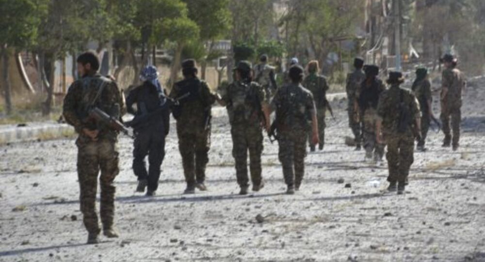 In this undated photo released Thursday, May 11, 2017, by Hawar News, the news agency for the semi-autonomous Kurdish areas in Syria, shows fighters from the Kurdish-led Syria Democratic Forces, patrolling on a street in Tabqa, northern Syria