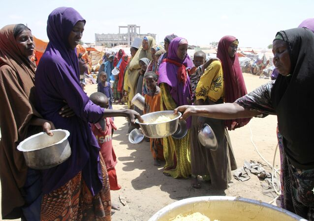 Displaced Somali women stand in a queue to receive food handouts in a camp outside of Mogadishu, Somalia, Monday, March, 27, 2017