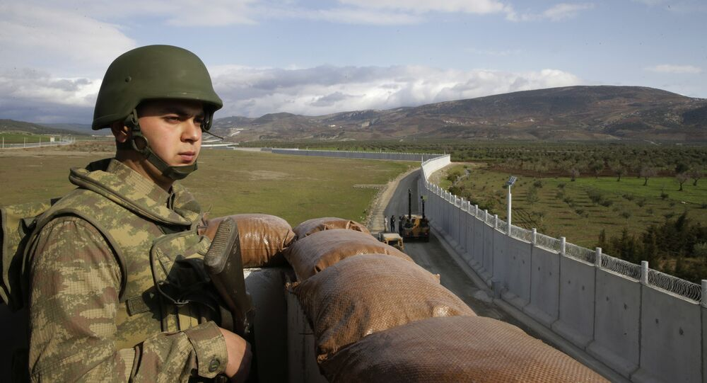 A Turkish army soldier mans an outpost near the town of Kilis, southeastern Turkey, adjacent to the wall the country had been constructing to boost security along its border with conflict-stricken Syria, background, Thursday, March 2, 2017