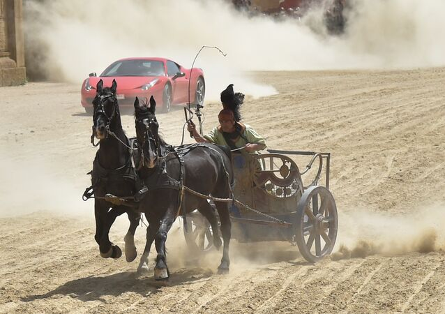 Ferrari driver Fabio Barone steers his Ferrari 458 Italia during a race against a Roman chariot drawn by two horses on Ben Hur movie set at Cinecitta World amusement park on May 11, 2017 in Castel Romano near Rome.