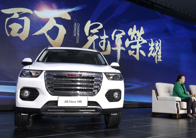 In this Sunday, Feb. 19, 2017 photo, Wei Jianjun, chairman of Great Wall Motors Ltd., second from right, speaks as a newly unveiled Haval SUV H6 model is displayed during a reception celebrating it sales passing the one million mark, at Great Wall headquarters in Baoding in north China's Hebei province.