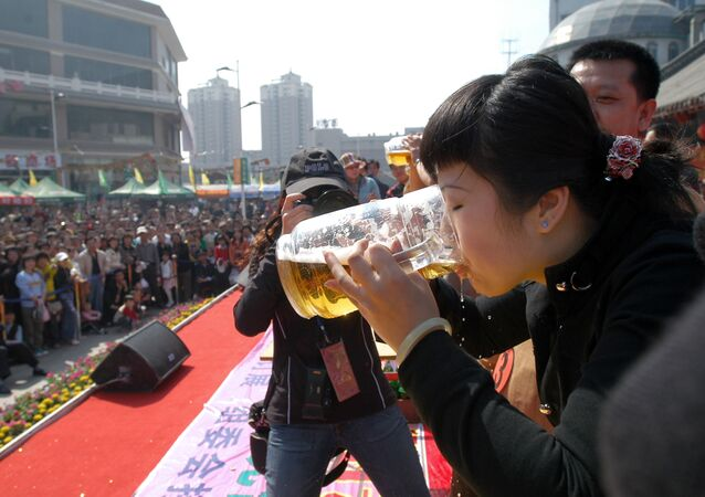 A Chinese woman downs a jug of beer during a beer drinking contest in Shenyang, northeastern China's Liaoning province (File)