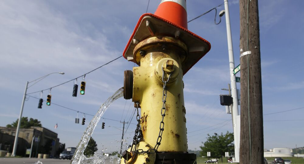 A road pylon caps the top of a fire hydrant being serviced, Thursday, June 26, 2014, in Cincinnati.