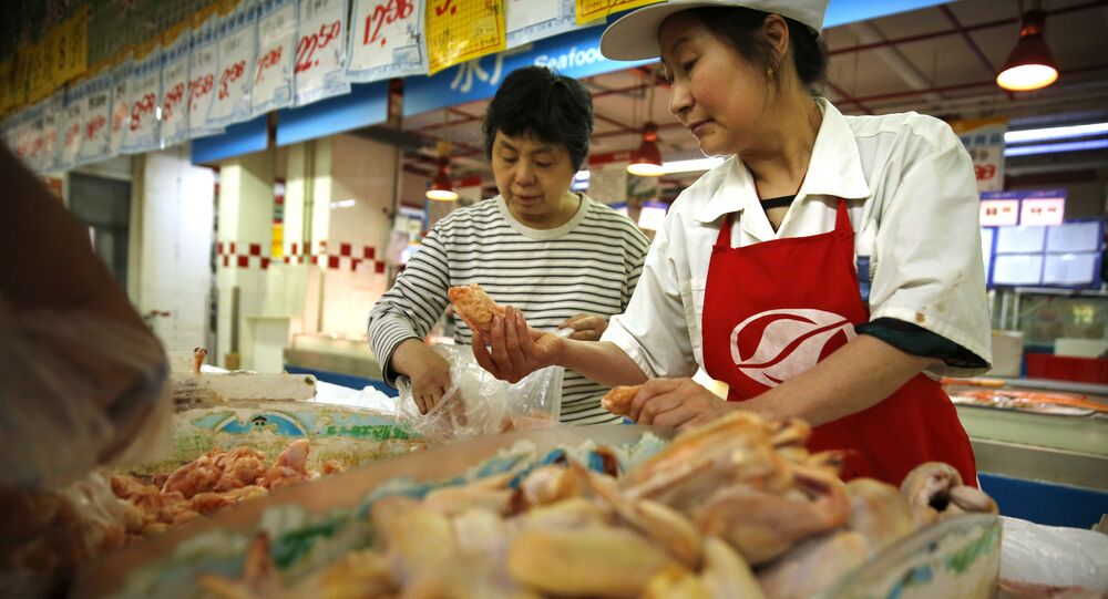 A clerk, right, helps a woman shop for chicken at a supermarket in Beijing, Friday, May 12, 2017
