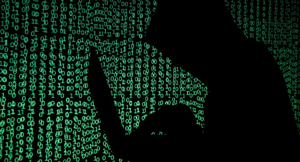 A hooded man holds a laptop computer as cyber code is projected on him in this illustration picture taken on May 13, 2017