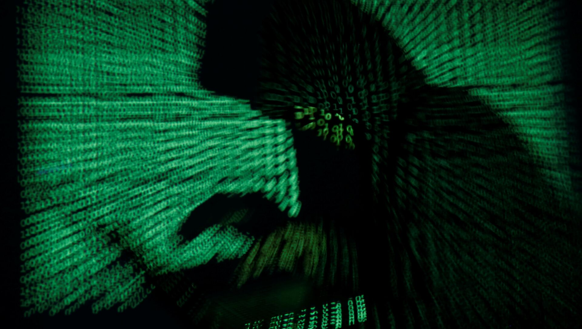 A hooded man holds a laptop computer as cyber code is projected on him in this illustration picture taken on May 13, 2017 - Sputnik International, 1920, 26.07.2021