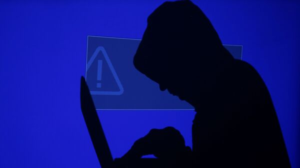 A hooded man holds a laptop computer as blue screen with an exclamation mark is projected on him in this illustration picture taken on May 13, 2017 - Sputnik International