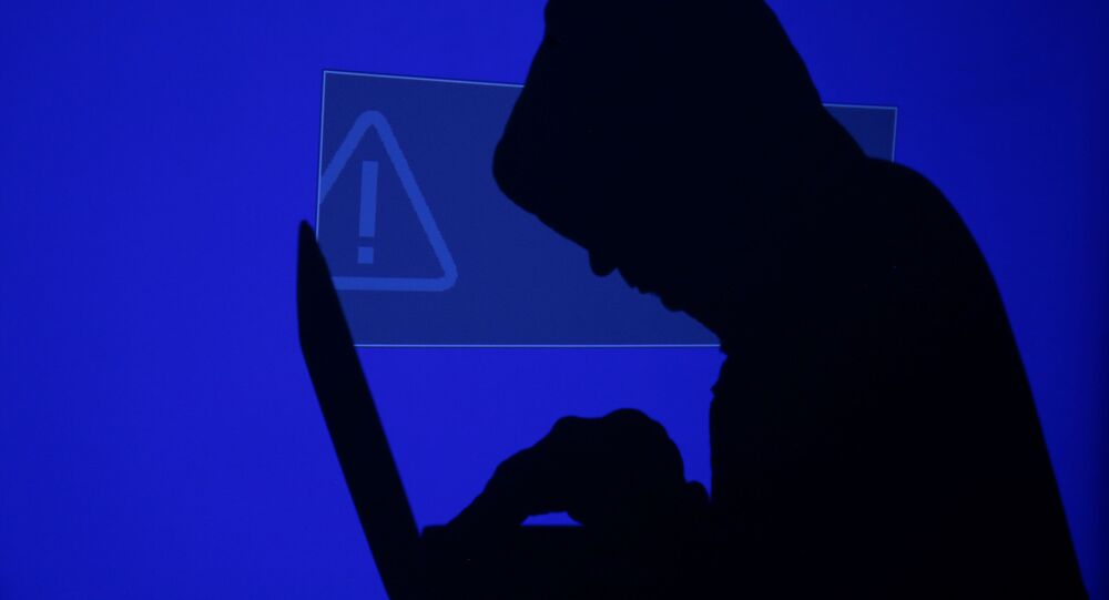 A hooded man holds a laptop computer as blue screen with an exclamation mark is projected on him in this illustration picture taken on May 13, 2017