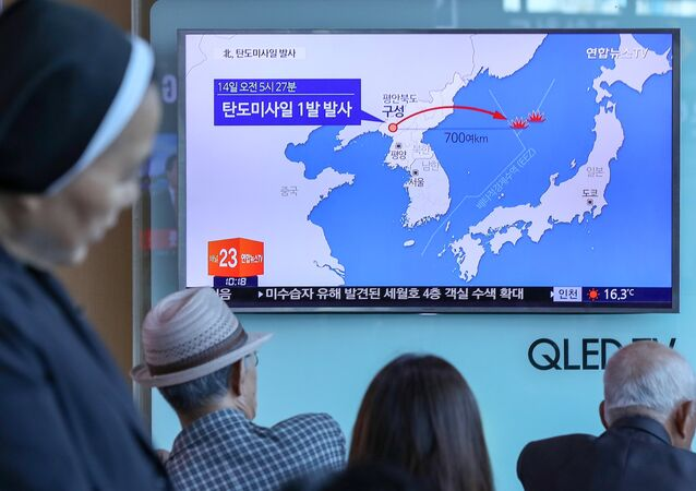 FILE PHOTO - People watch a news report on North Korea firing a ballistic missile, at a railway station in Seoul, South Korea, May 14, 2017
