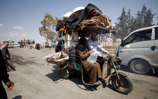 Internally displaced people who fled Raqqa city ride a tricycle with their belongings as they leave a camp in Ain Issa, Raqqa Governorate, Syria May 4, 2017 - Sputnik International