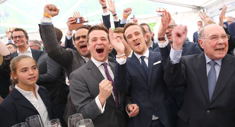 (L-R) Julius and Johannes Laschet, Sons of Armin Laschet, top candidate of the Christian Democratic Union (CDU) and his father Heinz Laschet react on first exit polls after the regional state elections of North Rhine-Westphalia, in Duesseldorf, May 14, 2017