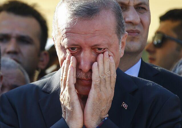 Turkish President Recep Tayyip Erdogan, right, wipes his tears