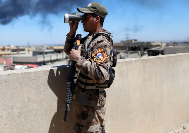 An Iraqi Counter Terrorism Services (CTS) soldier looks though binoculars during a battle between CTS and Islamic State militants in western Mosul, Iraq, April 25, 2017.