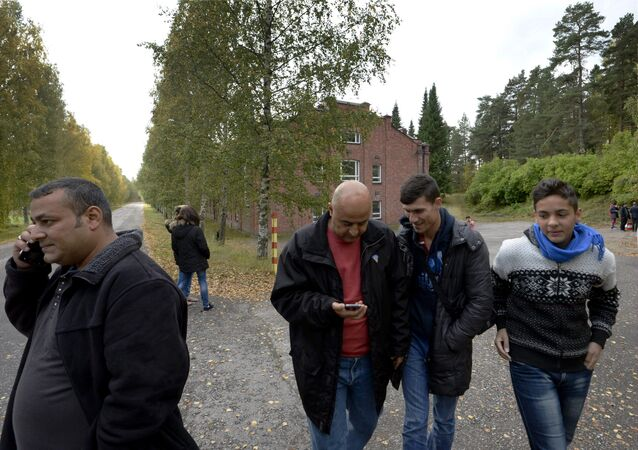 In this photo taken Friday, Sept. 25, 2015, Iraqi asylum seekers stand outside a refugee center located in the former army barracks, Lahti, Finland. Finland